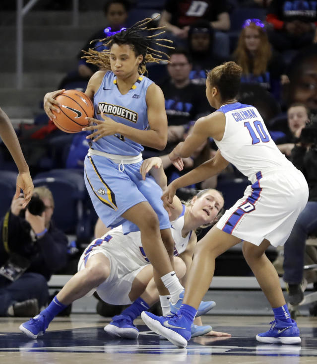 Marquettes' Amani Wilborn, left, spins out away from the defense of DePaul's Amarah Coleman (10) and Kelly Campbell during the first half of an NCAA college basketball game in the championship of the Big East conference tournament, Tuesday, March 6, 2018, in Chicago. (AP Photo/Charles Rex Arbogast)