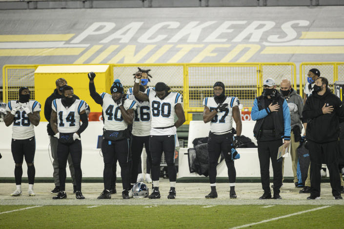 FILE - Carolina Panthers players stand for the National Anthem during an NFL football game against the Green Bay Packers in Green Bay, Wis., in this Saturday, Dec. 19, 2020, file photo. The national anthem would have to be played before all sporting events at Lambeau Field, the Fiserv Forum and all other Wisconsin venues that have received taxpayer money under a bill introduced Thursday, Feb. 25, 2021, in the state Legislature by a Republican lawmaker. (AP Photo/Jeffrey Phelps, File)