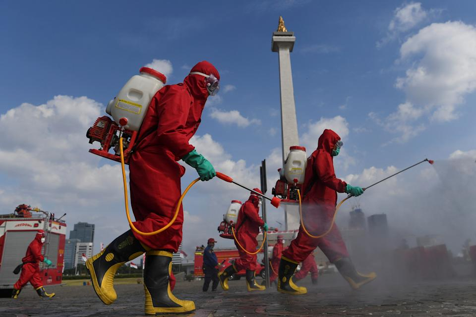 Firefighters wearing protective suits spray disinfectant at the National Monument area to prevent the spread of the coronavirus disease (COVID-19) in Jakarta, Indonesia June 17, 2020, in this photo taken by Antara Foto/Wahyu Putro/via REUTERS. ATTENTION EDITORS - THIS IMAGE WAS PROVIDED BY THIRD PARTY. MANDATORY CREDIT. INDONESIA OUT.     TPX IMAGES OF THE DAY
