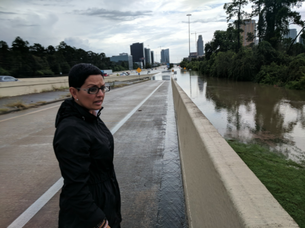 Rosanna Moreno looks over the flooded Buffalo Bayou on Interstate 610. (Roque Planas/HuffPost)