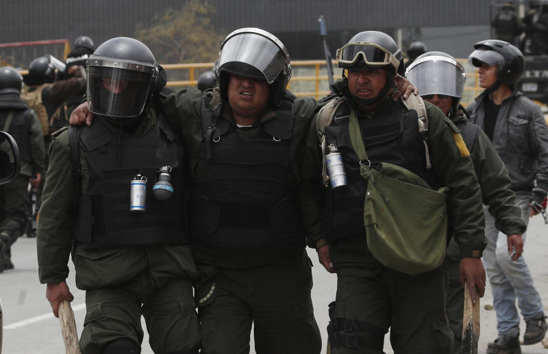 Police help an injured colleague during clashes with supporters of former President Evo Morales in La Paz, Bolivia, Monday, Nov. 11, 2019. Morales' Nov. 10 resignation, under mounting pressure from the military and the public after his re-election victory triggered weeks of fraud allegations and deadly demonstrations, leaves a power vacuum and a country torn by protests against and for his government. (AP Photo/Juan Karita)