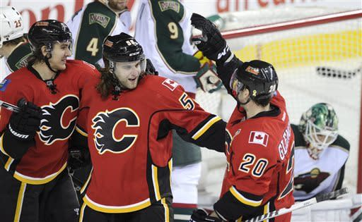 Calgary Flames' Ben Hanowski, center, celebrates his first NHL goal with Curtis Glencross, right, and Mikael Backlund, from Sweden, during the third period of an NHL hockey game against the Minnesota Wilde in Calgary, Alberta, Monday, April 15, 2013. (AP Photo/The Canadian Press, Larry MacDougal)