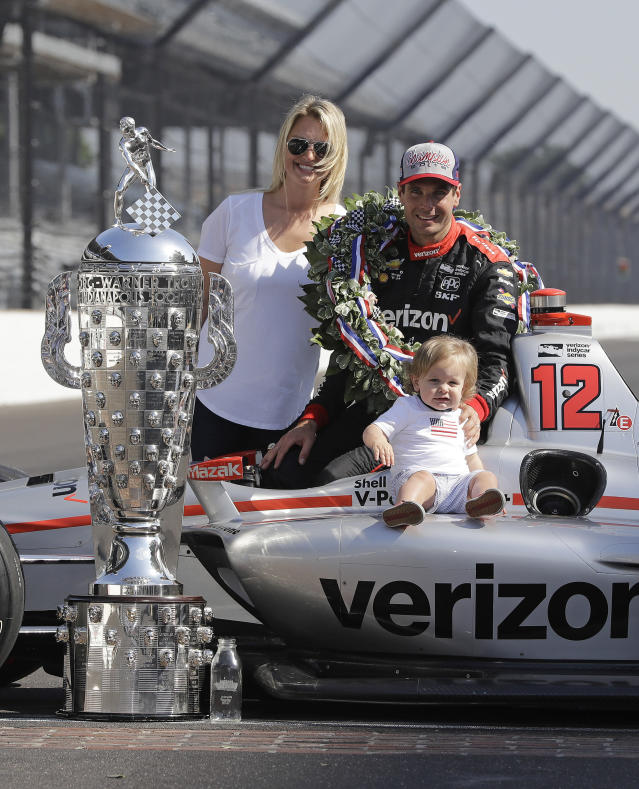 Indianapolis 500 champion Will Power, of Australia, poses with his wife, Liz, and son, Beau, with the Borg-Warner Trophy during the traditional winners photo session on the start/finish line at the Indianapolis Motor Speedway, Monday, May 28, 2018, in Indianapolis. (AP Photo/Darron Cummings)
