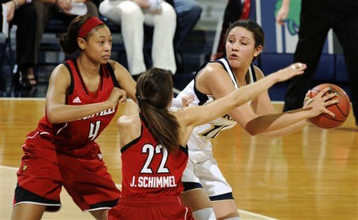 Notre Dame forward Natalie Achonwa, right, throws a pass around Louisville guards Antonita Slaughter, left, and Jude Schimmel in the first half of an NCAA college basketball game, Monday, Feb. 11, 2013, in South Bend, Ind. (AP Photo/Joe Raymond)