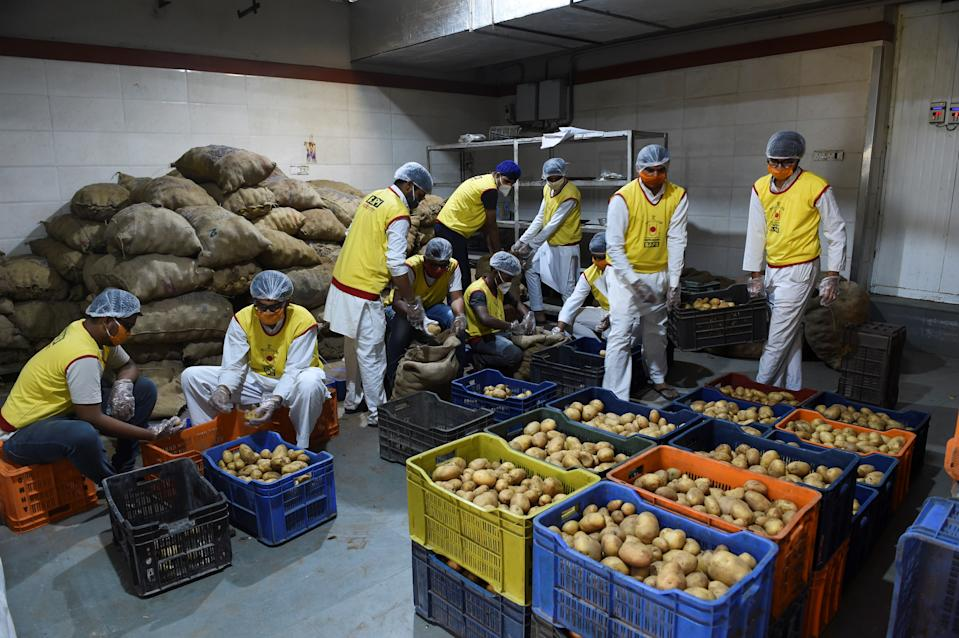 Volunteers of the Bochasanwasi Akshar Purushottam Sanstha (BAPS) prepare vegetables for distributing among poor residents during a government-imposed nationwide lockdown as a precautionary measure against the COVID-19 novel coronavirus in Ahmedabad on March 28, 2020. (Photo by Sam PANTHAKY / AFP) (Photo by SAM PANTHAKY/AFP via Getty Images)