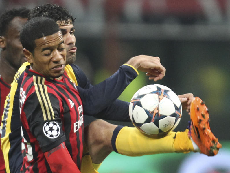 Atletico Madrid Brazilian forward Diego Costa, right, vies for the ball with AC Milan midfielder Urby Emanuelson, of the Netherlands, during a Champions League, round of 16, first leg, soccer match between AC Milan and Atletico Madrid at the San Siro stadium in Milan, Italy, Wednesday, Feb. 19, 2014. (AP Photo/Antonio Calanni)