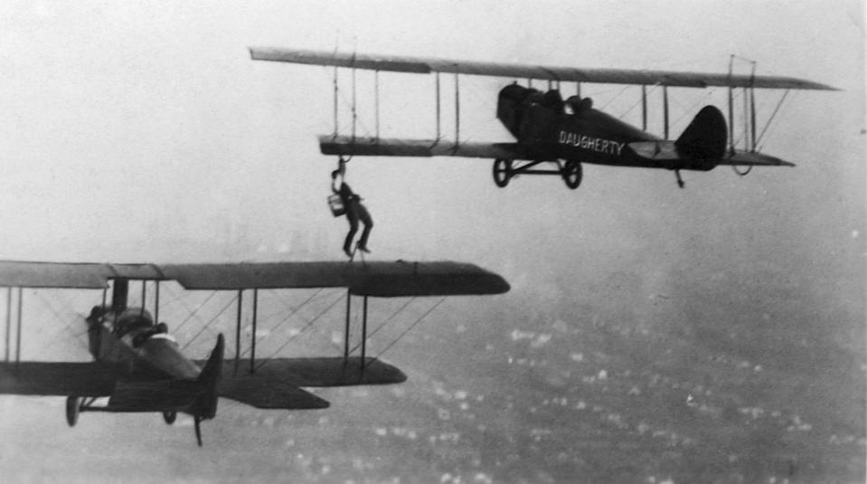 <p>A man performs the daring task of climbing atop the wing of his plane to refuel another while in mid-air.</p>