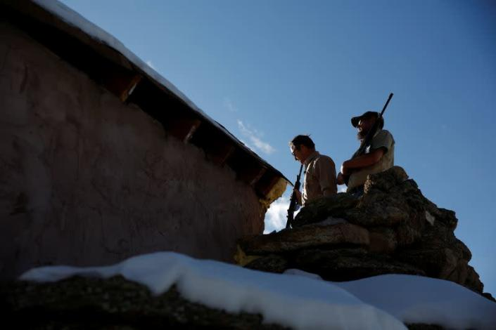 Drew Miller and Kacey Dawson stand on a lookout perch holding weapons at a survival camp