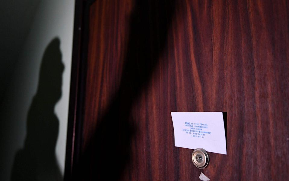 A card with contacts of a local police chief fixed to the door of the flat of Mr Navalny - NATALIA KOLESNIKOVA/AFP