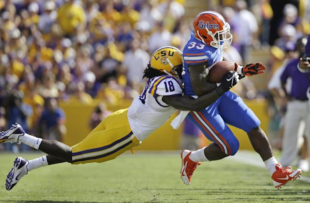Florida running back Mack Brown (33) is tackled by LSU linebacker Lamin Barrow (18) in the first half of an NCAA college football game in Baton Rouge, La., Saturday, Oct. 12, 2013. (AP Photo/Gerald Herbert)