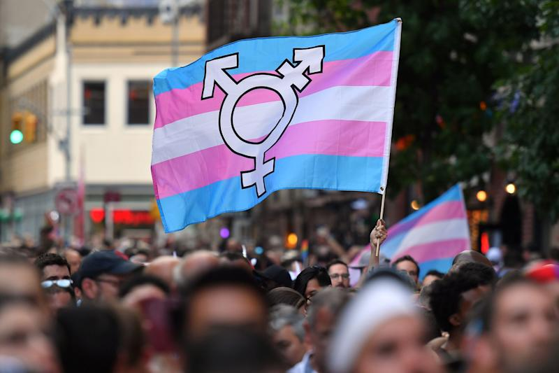A rally-goer waves a transgender pride flag outside of the Stonewall Inn during a march to commemorate the 50th anniversary of the Stonewall Riots in New York, June 28, 2019.