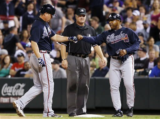 Atlanta Braves' Chipper Jones, front left, is congratulated by first base coach Terry Pendleton, front right, after Jones drove in two runs with a single against the Colorado Rockies in the seventh inning of a baseball game in Denver, Saturday, May 5, 2012. First base umpire Brian Runge, rear, looks on. (AP Photo/David Zalubowski)