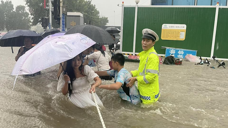 A traffic police officer guides residents to cross a flooded road with a rope during heavy rainfall in Zhengzhou, Henan province, China July 20, 2021. Picture taken July 20, 2021. China Daily via REUTERS  ATTENTION EDITORS - THIS IMAGE WAS PROVIDED BY A THIRD PARTY. CHINA OUT.