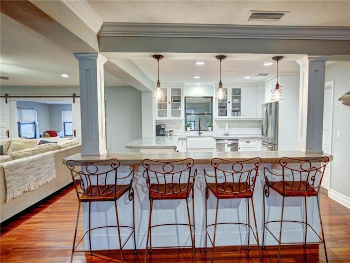 the kitchen with concrete countertops, four stools, white cabinets, and light fixtures next to the living toom