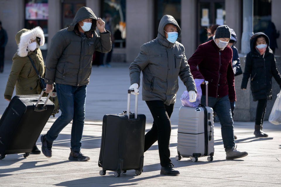 Travelers wearing face masks to protect against the spread of the coronavirus walk with their luggage at the Beijing Railway Station in Beijing, Thursday, Jan. 28, 2021. Efforts to dissuade Chinese from traveling for Lunar New Year appeared to be working. Beijing's main train station was largely quiet on the first day of the travel rush and estimates of passenger totals were smaller than in past years. (AP Photo/Mark Schiefelbein)