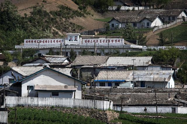 <p>North Korean buildings and houses, one with the images of late leaders Kim Il-Sung and Kim Jung-Il father, are seen in a village north of the border city of Dandong, Liaoning province, northern China on May 24, 2017 in Dandong, China. (Photo: Kevin Frayer/Getty Images) </p>
