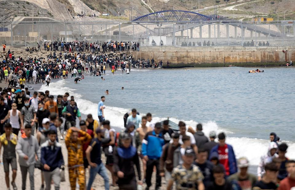 Migrants are pictured between Morocco and the Spanish enclave of Ceuta on May 18, 2021 in Fnideq. - At least 5,000 migrants, an unprecedented influx at a time of high tension between Madrid and Rabat, slipped into Ceuta on May 17, a record for a single day, Spanish authorities said. They reached the enclave by swimming or by walking at low tide from beaches a few kilometres to the south, some using inflatable swimming rings and rubber dinghies. (Photo by FADEL SENNA / AFP) (Photo by FADEL SENNA/AFP via Getty Images) (Photo: FADEL SENNA via Getty Images)