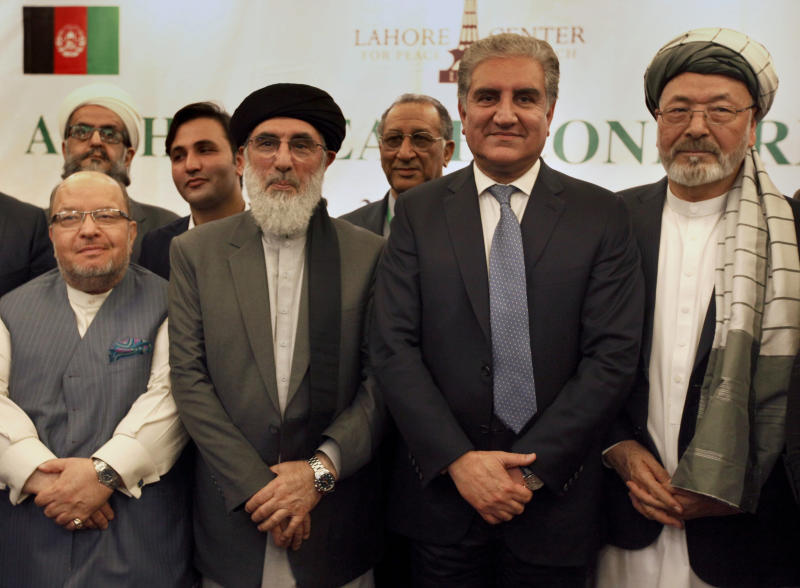 Afghan politicians and other participants pose for photograph with Pakistani Foreign Minister Shah Mahmood Qureshi, second right, after the opening session of an Afghan Peace Conference in Bhurban, 65 kilometers (40 miles) north of Islamabad, Pakistan, Saturday, June 22, 2019. Dozens of Afghan political leaders attended a peace conference in neighboring Pakistan on Saturday to pave the way for further Afghan-to-Afghan dialogue. (AP Photo/Anjum Naveed)