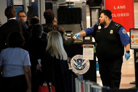 FILE PHOTO - TSA officer checks travelers at LaGuardia Airport in New York City is seen after after hundreds of flights were delayed or grounded in New York