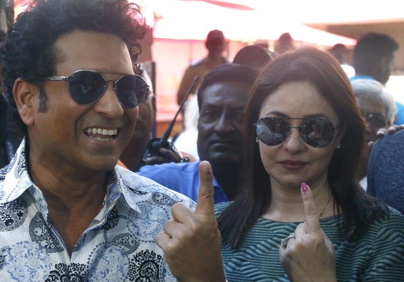 Former Indian cricketer Sachin Tendulkar, left, with his wife Anjali pose for media after casting their votes in Mumbai, India, Monday, Oct. 21, 2019. Voting is underway in two Indian states of Maharashtra in the west and Haryana in the north where the Hindu nationalist Bharatiya Janata Party (BJP) headed by prime minister Narendra Modi is trying to win a second consecutive term. (AP Photo/Rafiq Maqbool)