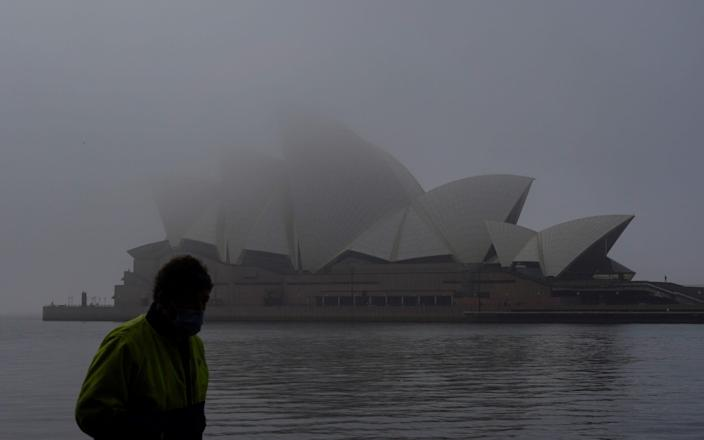 A man wearing a protective face mask walks past the Sydney Opera House, seen shrouded in fog, during a lockdown to curb the spread of a coronavirus disease (COVID-19) outbreak in Sydney, Australia, July 1, 2021. - Reuters