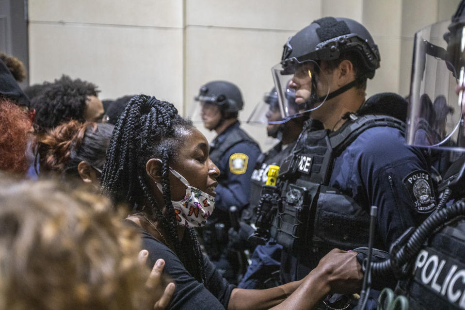 A protester holds a police officer's hand while praying together during a rally to protest the deaths of George Floyd and Breonna Taylor in Lexington, Ky., on Sunday, May 31, 2020. (Ryan C. Hermens/Lexington Herald-Leader via AP)