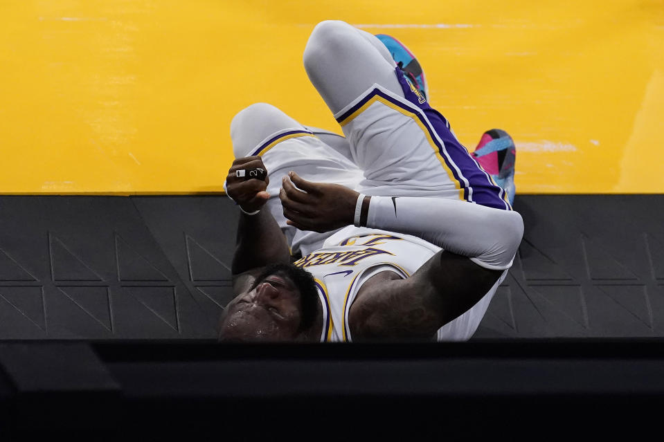Los Angeles Lakers forward LeBron James rolls off the court after going down with an injury during the first half of an NBA basketball game against the Atlanta Hawks Saturday, March 20, 2021, in Los Angeles. (AP Photo/Marcio Jose Sanchez)