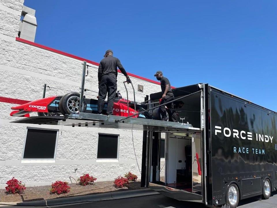 Members of the Force Indy race team load up the No. 99 car onto the team's transporter ahead of the season-opener at Barber Motorsports Park.