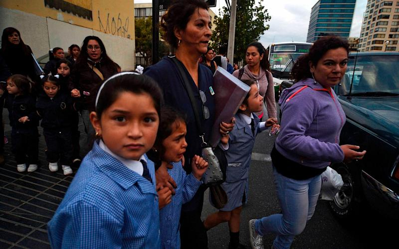 Women and schoolchildren evacuate a building during the quake in Vina del Mar, Chile - AFP