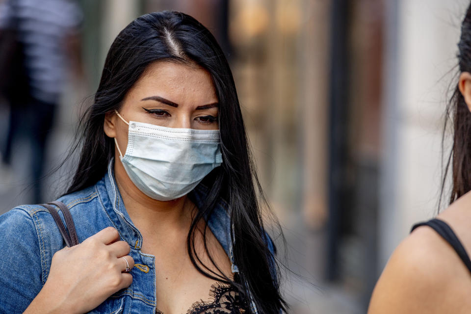 ANTWERP, BELGIUM - 2020/07/20: A woman wearing a face mask as a preventive measure walks on the street during the coronavirus crisis. The wearing of a face mask will become compulsory from Saturday in shops and some other indoor spaces where people gather. (Photo by Robin Utrecht/SOPA Images/LightRocket via Getty Images)
