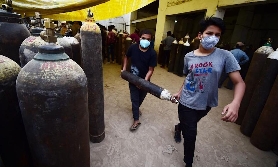 People carry a medical oxygen cylinder at a refilling station in Allahabad.