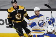 Buffalo Sabres' Riley Sheahan (15) celebrates his short-handed goal in front of Boston Bruins' Matt Grzelcyk (48) during the first period of an NHL hockey game, Saturday, May 1, 2021, in Boston. (AP Photo/Michael Dwyer)