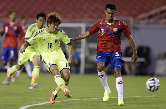 Japan forward Yuya Osako (18) gets off a shot in front of Costa Rica defender Giancarlo Gonzalez (3) during the first half of a friendly soccer match Monday, June 2, 2014, in Tampa, Fla. (AP Photo/Chris O'Meara)