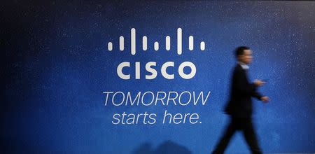 A visitor walks past a Cisco advertising panel at the Mobile World Congress in Barcelona