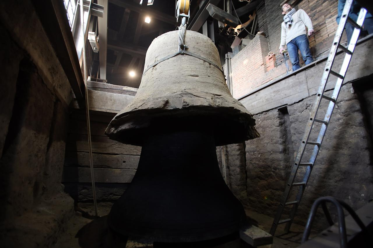 "The new bell bound for Notre Dame cathedral in Paris, ""Gabriel"" appears as the cope mould is lifter clear after being cast in the foundry of Villedieu les Poeles, Normandy, France, Friday, Dec. 7, 2012. Paris' Notre Dame Cathedral will be celebrating its 850th anniversary starting Wednesday Dec. 12, 2012, and Gabriel will join the peal of bells at the medieval landmark cathedral. (AP Photo/David Vincent)"