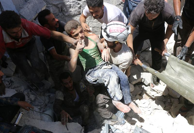 Syrian civil defence volunteers carry a young boy from the rubble following reported air strikes on the rebel-held neighbourhood of Al-Mashhad in Aleppo (AFP Photo/Thaer Mohammed)