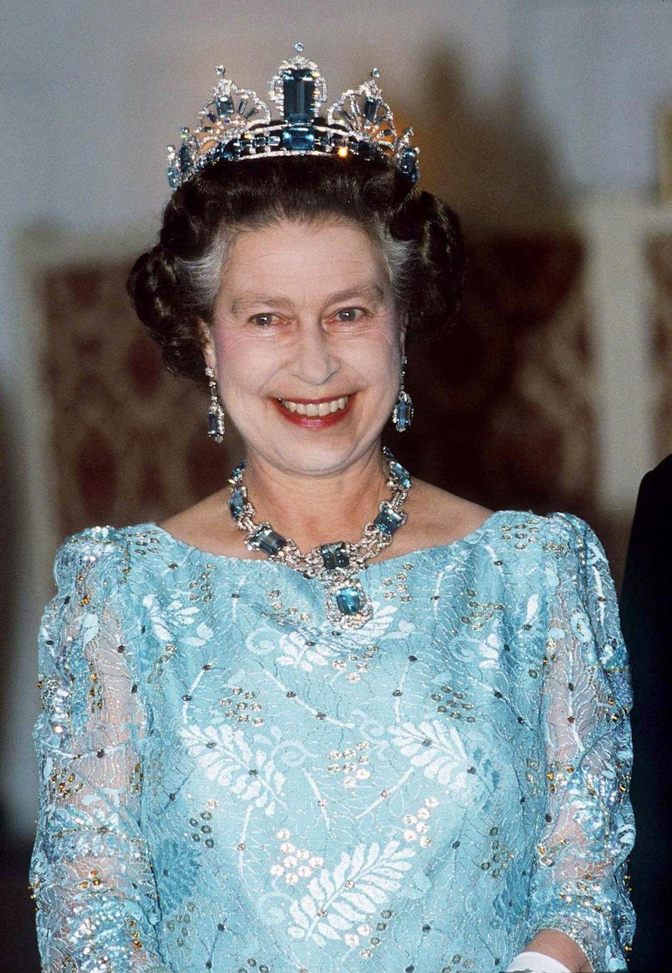 """<p>Here the Queen dons a diamond and aquamarine earrings, and necklace set, gifted to her by the People of Brazil for her coronation. <a href=""""http://orderofsplendor.blogspot.com/2013/03/tiara-thursday-brazilian-aquamarine.html"""" rel=""""nofollow noopener"""" target=""""_blank"""" data-ylk=""""slk:Four years later, she commissioned Garrard to make her a tiara that matches nicely"""" class=""""link rapid-noclick-resp"""">Four years later, she commissioned Garrard to make her a tiara that matches nicely</a>. The uprights are apparently detachable and could be used as brooches. She's seen wearing the set here on October 15, 1986.</p>"""