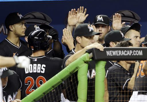 Miami Marlins' Greg Dobbs (29) is congratulated in the dugout after scoring on a single by Placido Polanco (not shown) in the ninth inning during a baseball game against the Arizona Diamondbacks in Miami, Friday, May 17, 2013. The Diamondbacks defeated the Marlins 9-2. (AP Photo/Lynne Sladky)