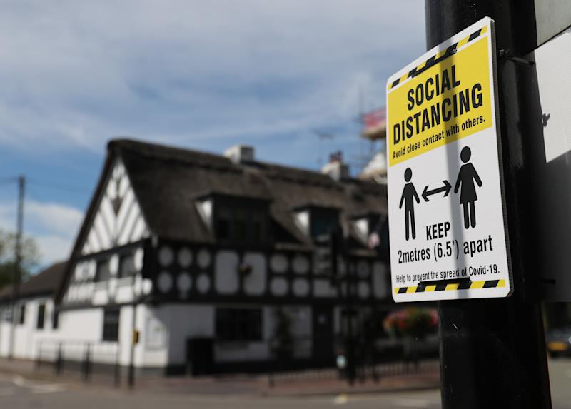A sign promoting social distancing is hung on a post near the Crown and Anchor pub following a spike in cases of the coronavirus disease (COVID-19) to visitors of the pub in Stone, Britain, July 30, 2020. REUTERS/Carl Recine