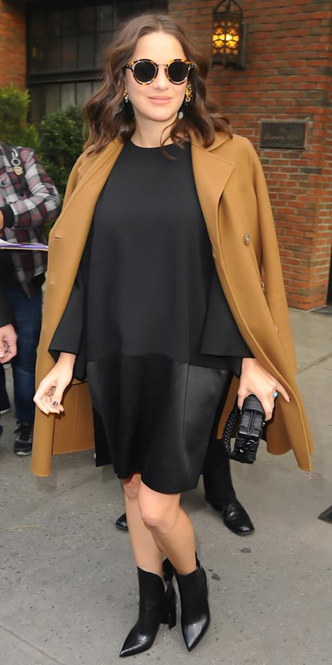The actress was snapped in the Big Apple wearing a flowing black top, leather skirt, and camel coat. Black accessories finished off her winning outfit.
