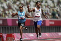 Adrian Ililau, of Palau, and Scott Fiti, of Federated States of Micronesia, compete in a heat in the men's 100-meter run at the 2020 Summer Olympics, Saturday, July 31, 2021, in Tokyo. (AP Photo/Petr David Josek)