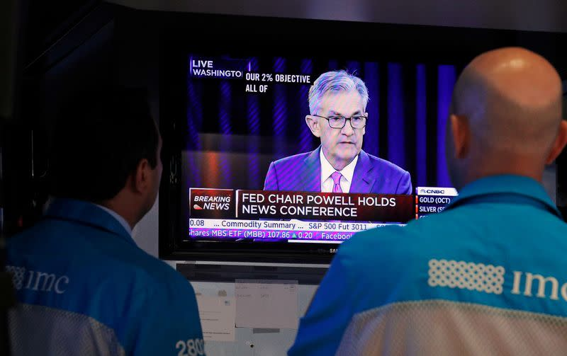 FILE PHOTO: Traders look on as a screen shows Federal Reserve Chairman Jerome Powell's news conference after the U.S. Federal Reserve interest rates announcement on the floor of the New York Stock Exchange (NYSE) in New York