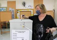 A woman casts her vote during parliamentary elections at a polling station in Nicosia
