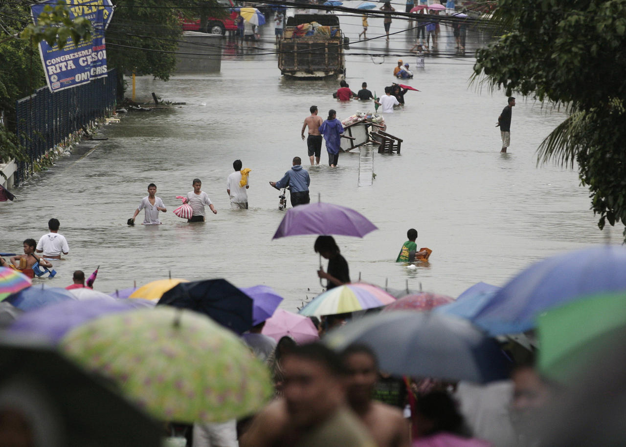 Residents wade along flooded roads in Quezon City, north of Manila, Philippines, on Tuesday Aug. 7, 2012. Relentless rains submerged half of the sprawling Philippine capital, triggered a landslide that killed several people and sent emergency crews scrambling Tuesday to rescue and evacuate tens of thousands of residents. (AP Photo/Aaron Favila)
