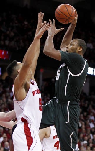 Michigan State's Adreian Payne, right, shoots against Wisconsin's Ryan Evans during the first half of an NCAA college basketball game Tuesday, Jan. 22, 2013, in Madison, Wis. (AP Photo/Andy Manis)