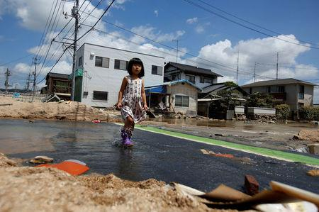 A local resident walks in a flood affected area in Mabi town in Kurashiki, Okayama Prefecture, July 10, 2018. REUTERS/Issei Kato