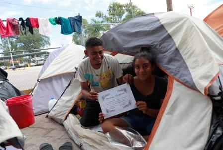 """Honduran migrants Marvin Madrid and his new wife Dexy Maldonado show their """"Marriage Certificate"""" during an interview with Reuters in an encampment in Matamoros"""