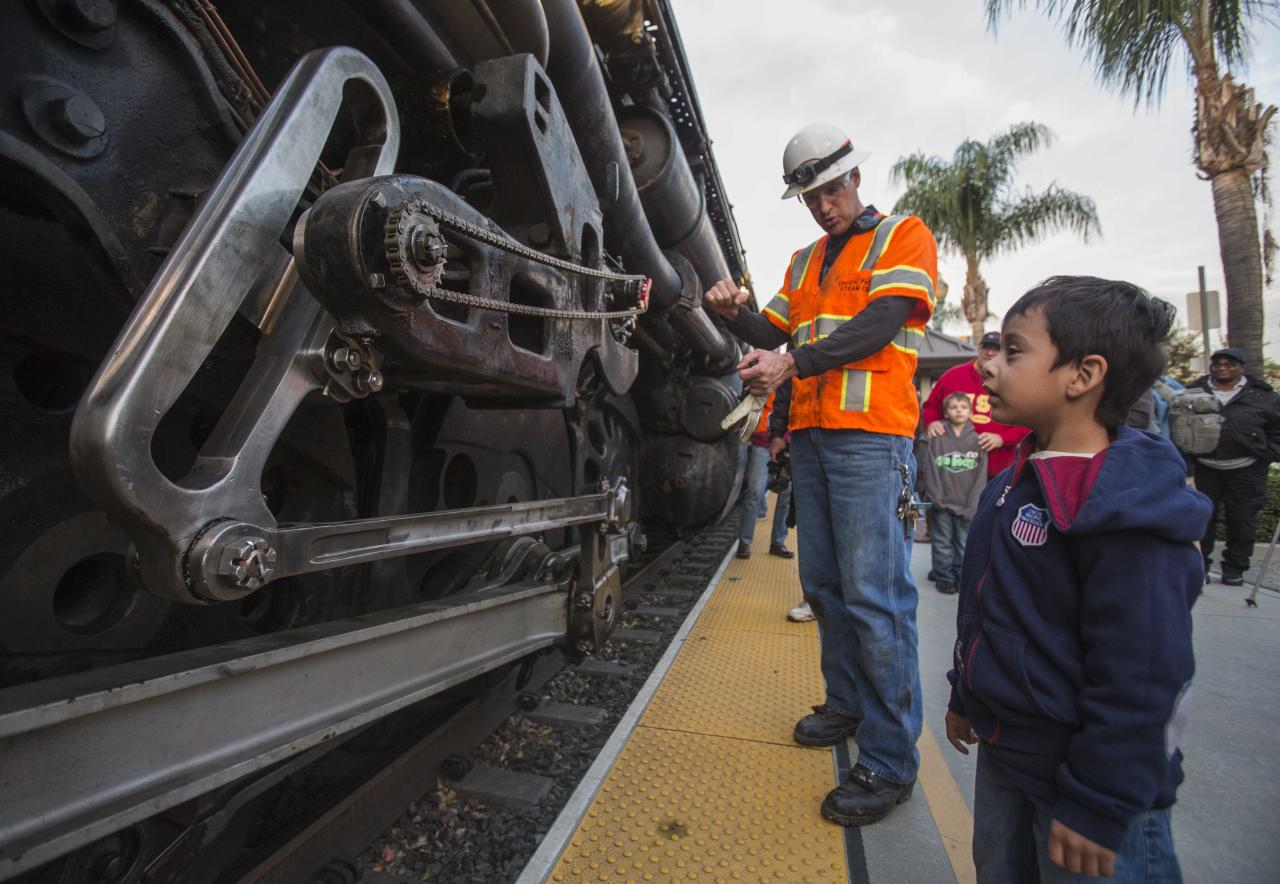 Miguel Angel Warner, right, 4, of Los Angeles, asks Ed Dickens, left, senior manager of Heritage Operations about the historic locomotive, Union Pacific Big Boy No. 4014 at Metrolink Station, Sunday, Jan. 26, 2014, in Covina, Calif. The 600-ton Big Boy locomotive left the Pomona fairgrounds on its way to a Union Pacific rail yard in Colton, about 60 miles away, where it will be available for two weekends of public viewing before moving on to Cheyenne, Wyo., for restoration work. The goal is to eventually get Engine 4014 back on the rails, said Union Pacific spokesman Aaron Hunt. (AP Photo/Ringo H.W. Chiu)