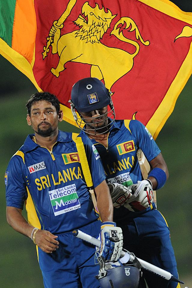 Sri Lankan cricketer Tillakaratne Dilshan (L) and Dinesh Chandimal walks back to the pavilion after their victory during the opening one-day international (ODI) match between Sri Lanka and Bangladesh at The Suriyawewa Mahinda Rajapakse International Cricket Stadium in the southern district of Hambantota on March 23, 2013.  Sri Lankan cricket captain Angelo Mathews  won the toss and elected to field. AFP PHOTO/ Ishara S. KODIKARA        (Photo credit should read Ishara S.KODIKARA/AFP/Getty Images)