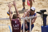 Alison Cerutti, right, of Brazil, takes a shot as Edgars Tocs, of Latvia, defends during a men's beach volleyball quarterfinal match at the 2020 Summer Olympics, Wednesday, Aug. 4, 2021, in Tokyo, Japan. (AP Photo/Petros Giannakouris)